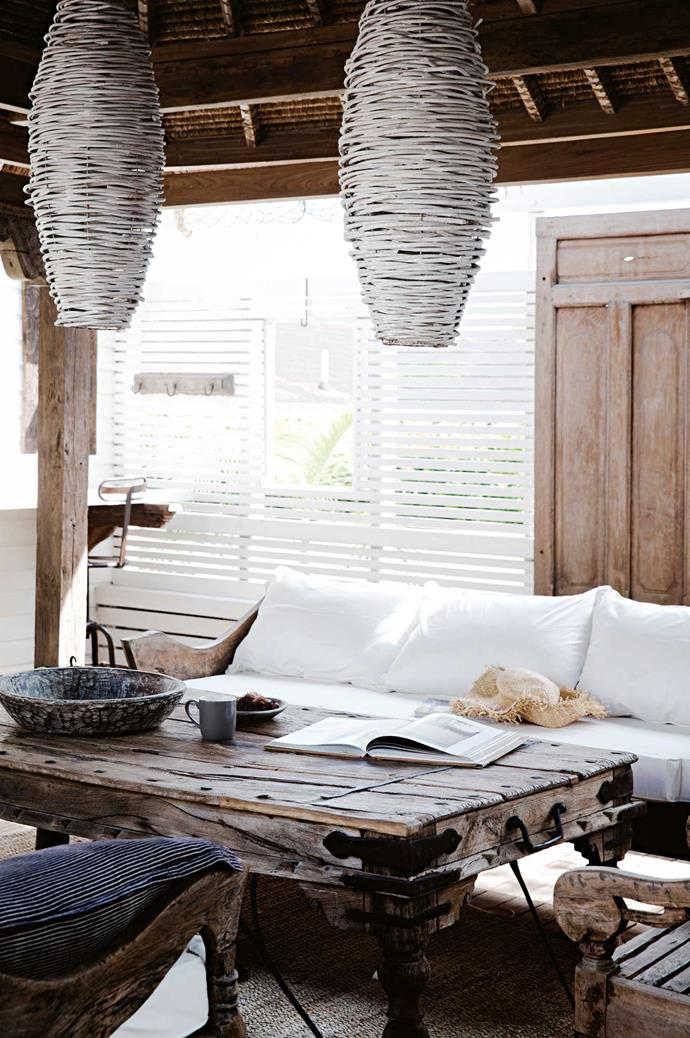 Balinese lampshades hang over an Indian table and Javanese tribal bench turned into a sofa.
