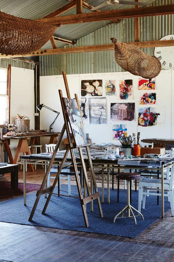 In the converted woolshed studio, Annie's easel stands beneath woven fish traps from Arnhem Land.
