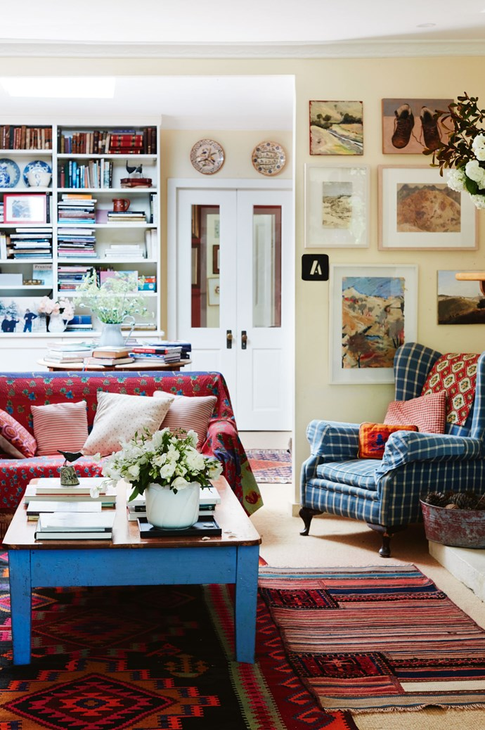 The living room rugs are from Morocco, while the armchair came from a garage sale and has been re-covered. Behind the chair, Annie's own work hangs next to artwork by Helen Gauchat and Elisabeth Cummings, as well as a special painting of boots by one of her students, Pam Dougherty. Annie cut down an old dining table to make the coffee table.