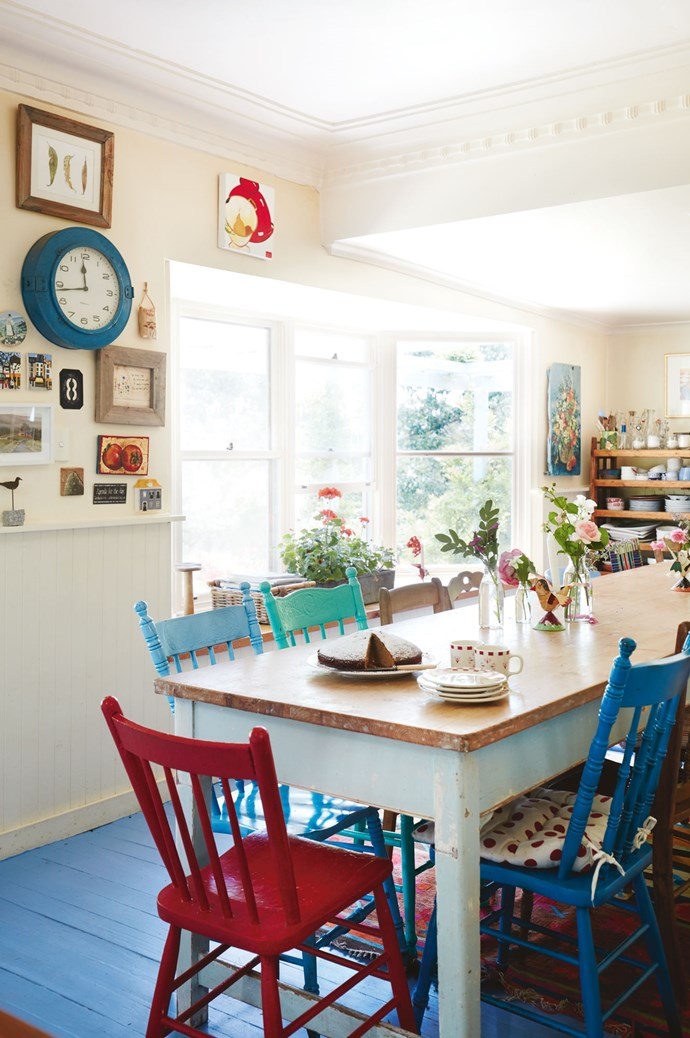 In the kitchen, the timber table from Elements I Love is thought to be an old pastry-rolling bench. It easily accommodates 16 people and is used for all meals and the occasional card game. Annie likes mismatched chairs and paints them different colours. She also painted the old railway clock on the wall. Plates are stored on an old fruit-drying rack behind the table.