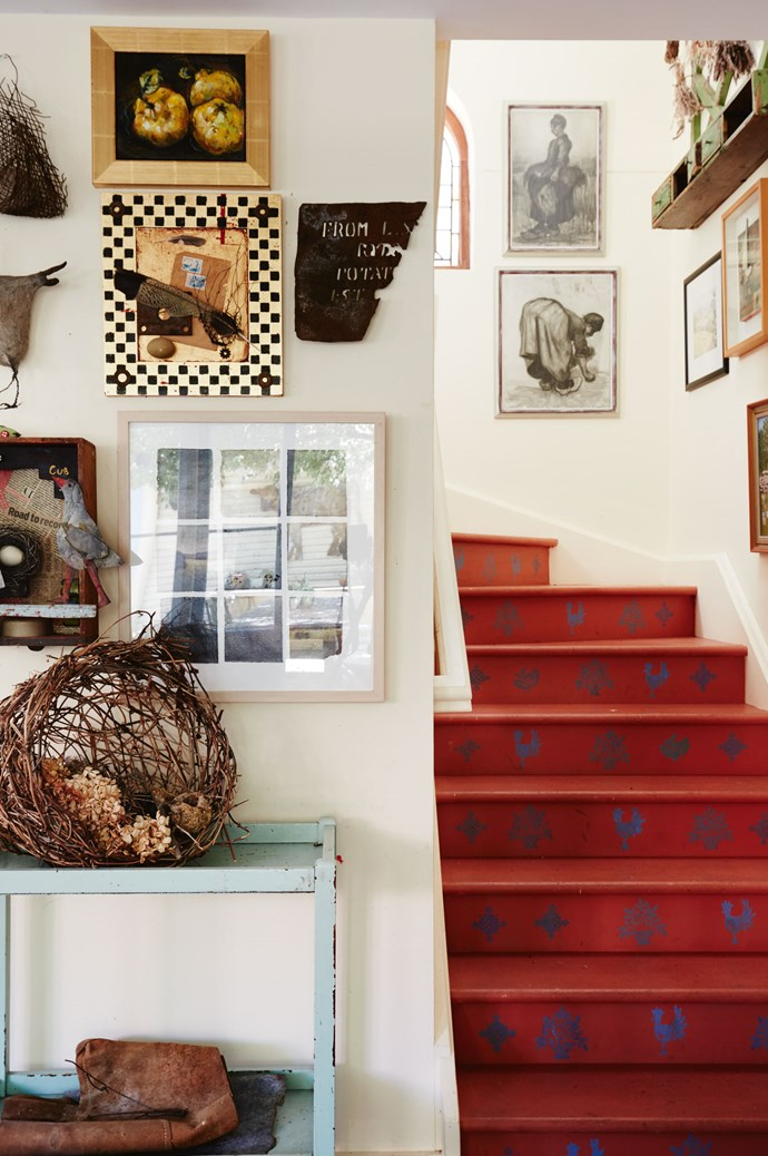 The unique red stairs have been stencilled using Annie's favourite French blue. Two Van Gogh prints hang above the stairs.