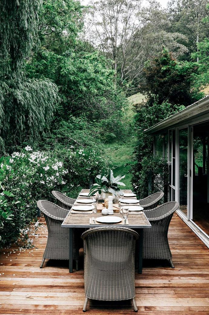 A spacious deck surrounded by flowering hedges has been furnished with a large dining table and wicker chairs.