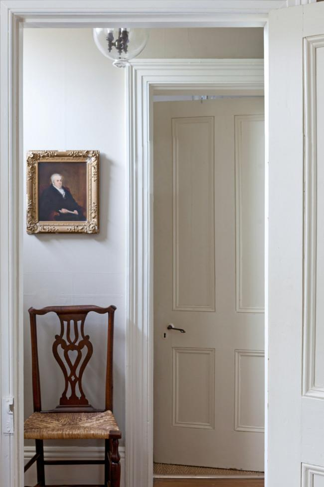 """Simon's beloved portrait of the Reverend Nicholas Ball - """"a Georgian gent!"""" - hangs in the hallway above an 18th-century rush-seated chair from England. The reproduction Hundi lamp was purchased from a Melbourne antique lighting dealer.   Photo: Simon Griffiths"""