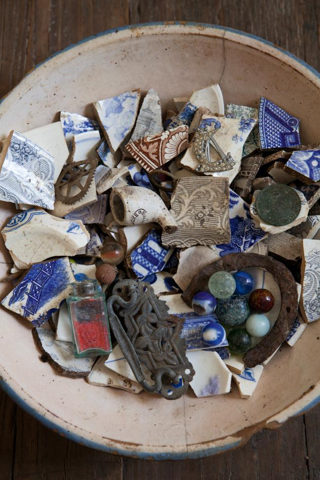 A bowl of 'treasures', including old coins and shards of china and bottles all dug from the garden.   Photo: Simon Griffiths