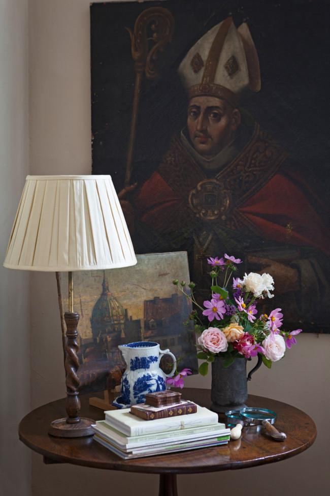 An old pewter tankard full of roses and cosmos from the garden sits on a George Ill oak tilt-top table. The portrait, subject unknown, is 17th or early 18th-century European, while the landscape on the table is a view of Florence.   Photo: Simon Griffiths