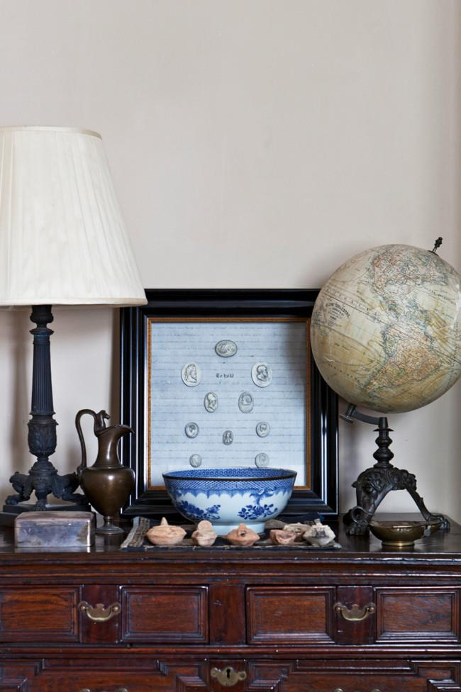 An antique oak chest of drawers supports more antique finds, including a French world globe, a collection of Roman oil lamps and an 18th-century Grand Tour collection of European plaster casts framed on antique vellum.   Photo: Simon Griffiths