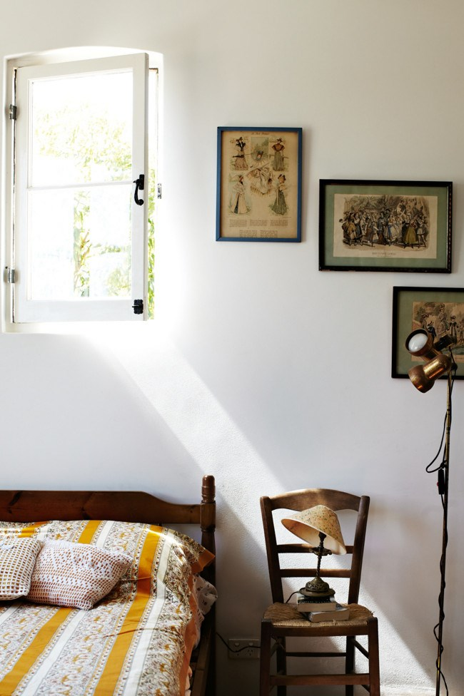 Pages from vintage French women's magazines decorate home owner Isabelle's bedroom. | Photo: Sharyn Cairns