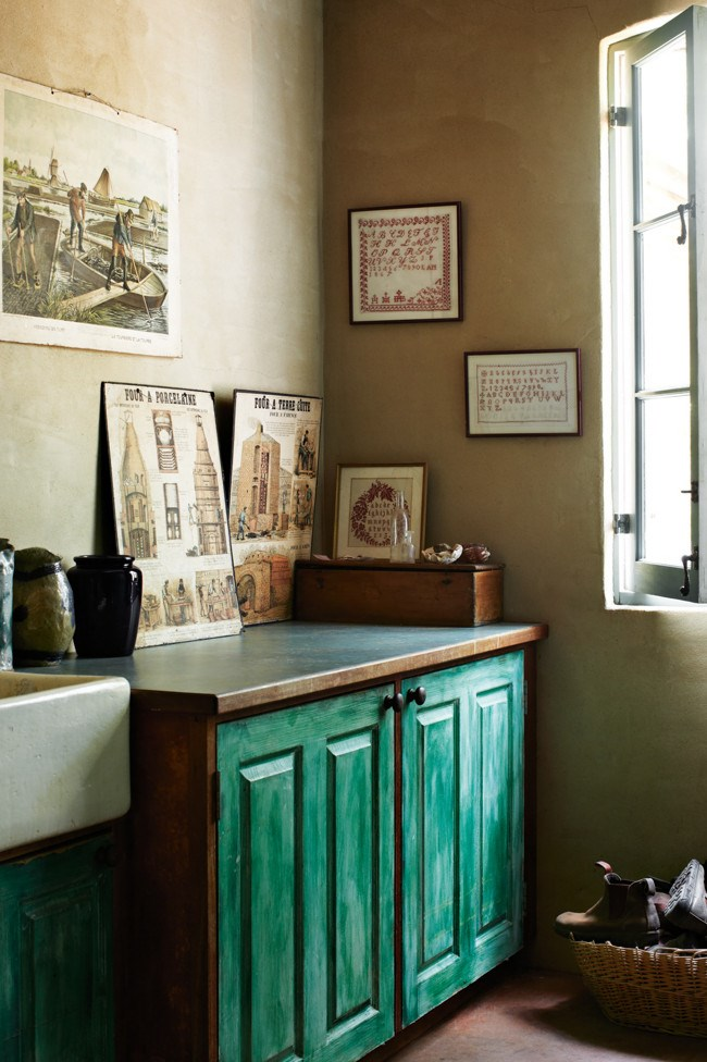 In the laundry, old industrial posters from Belgium sit above a cabinet painted in [Porter's Paints](http://www.porterspaints.com/) Antique Wash. | Photo: Sharyn Cairns