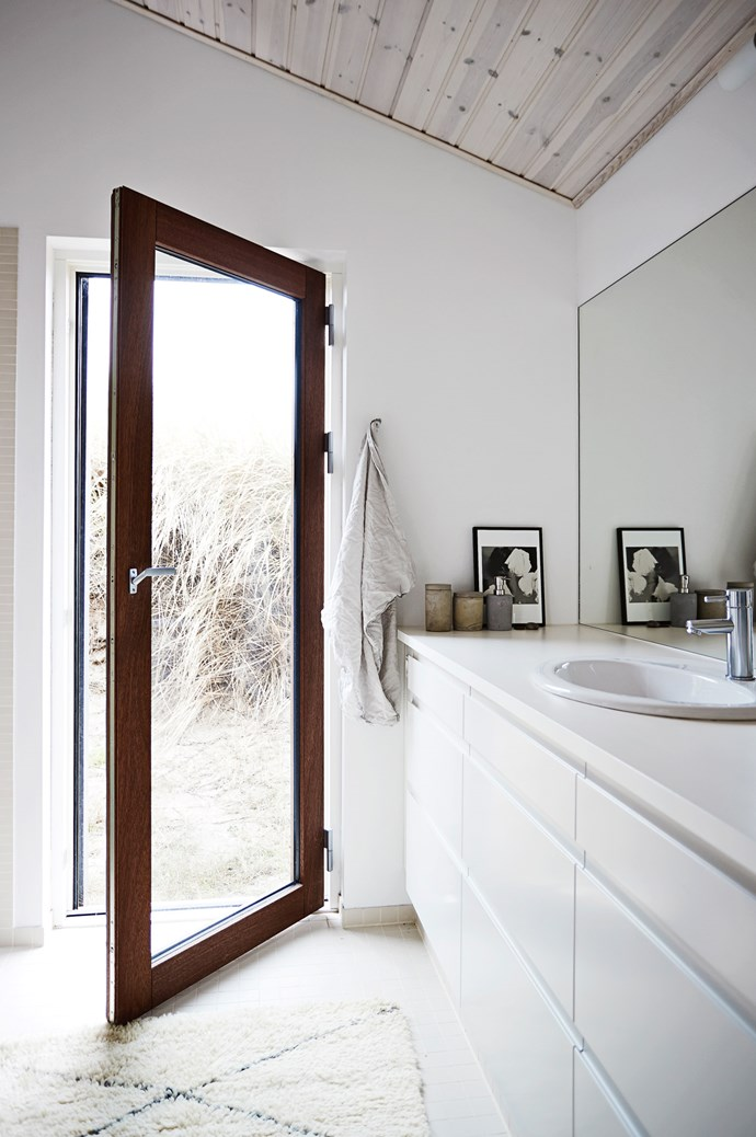 The bathroom features modern lines and understated cabinetry.