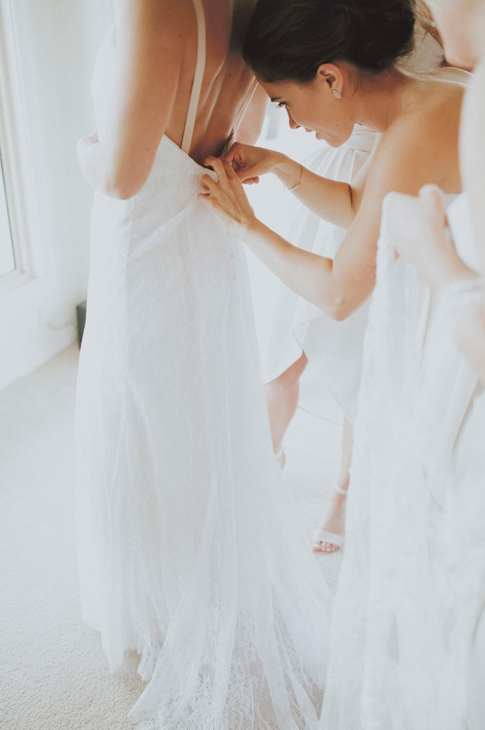 Bridesmaids help Lou into her bespoke silk and lace gown, a low-back A-line made by local Coolah dressmaker Bronwenn Douglas.   Photo: Feather and Birch Wedding Co