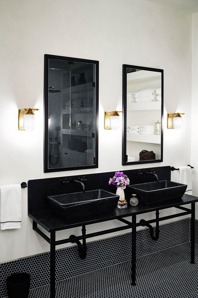 Black washstand sinks punctuate the room's gilded design scheme.  | Photo: Architectural Digest