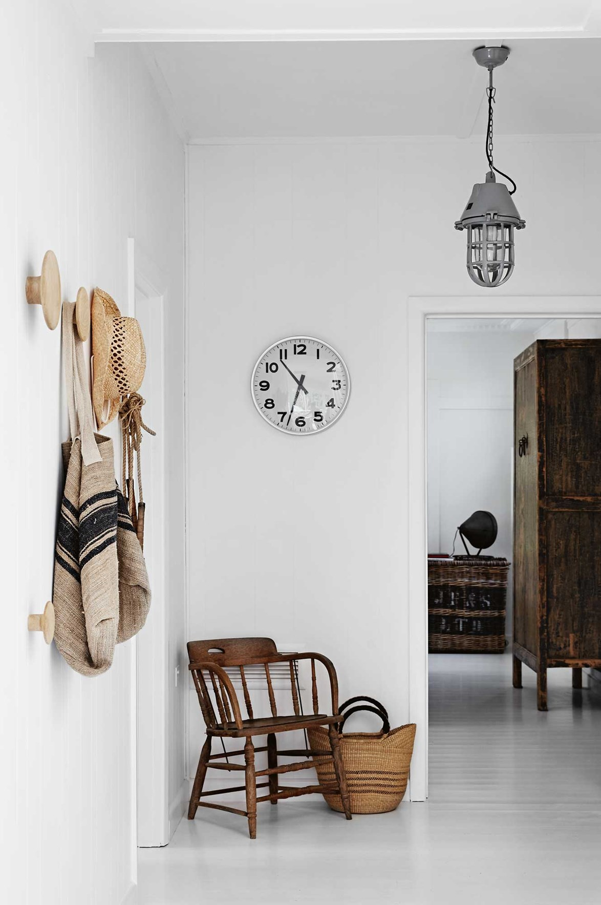 "This all-white, [European-style farmhouse](https://www.homestolove.com.au/european-farmhouse-style-13827|target=""_blank"") on the Mornington Peninsulas has been warmed up with pieces of antique timber furniture and an array of wicker baskets and bags in the light-filled entryway."