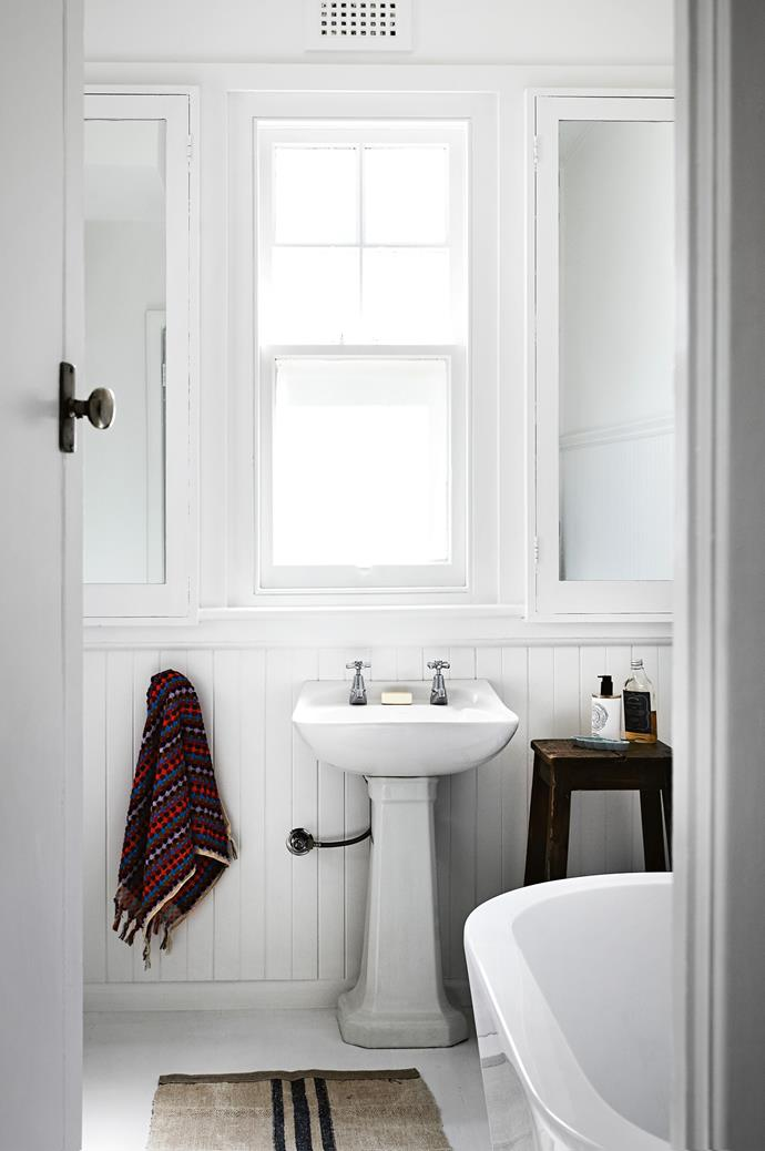 The bathroom features lining boards, a freestanding bathtub and a vintage pedestal basin.