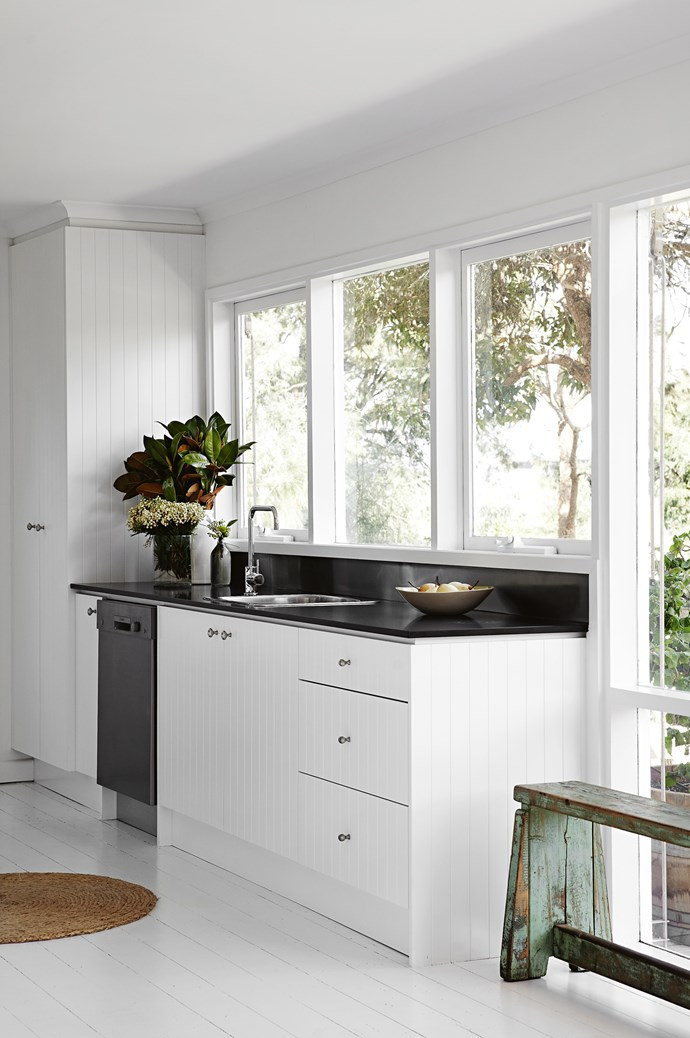 "A sleek bespoke [kitchen with tongue-and-groove door fronts](https://www.homestolove.com.au/kitchen-cabinet-door-styles-7021|target=""_blank"") is paired with a rustic, antique bench."