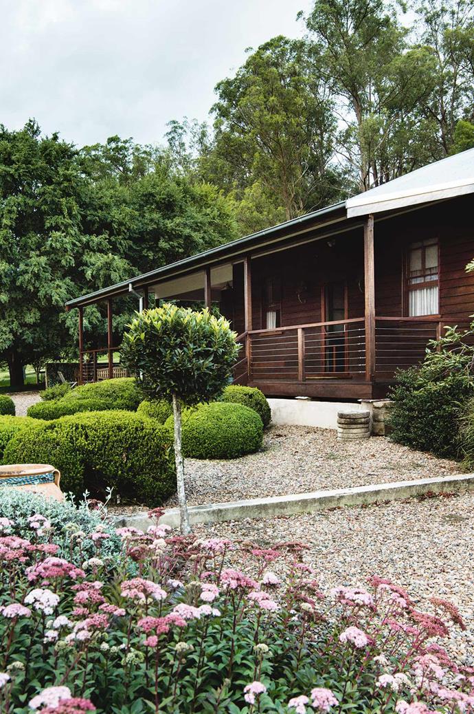"The [front verandah](https://www.homestolove.com.au/country-verandahs-13365|target=""_blank"") overlooks the landscaped garden."