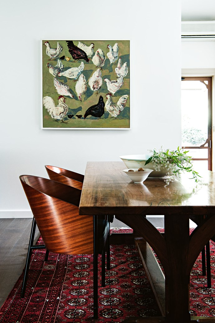 """'Chooks' by [Lucy Culliton](https://www.homestolove.com.au/farmhouse-garden-flowering-poppies-13751 target=""""_blank"""") hangs in the dining room above a Nicholas Dattner table made from recycled yellow stringybark."""