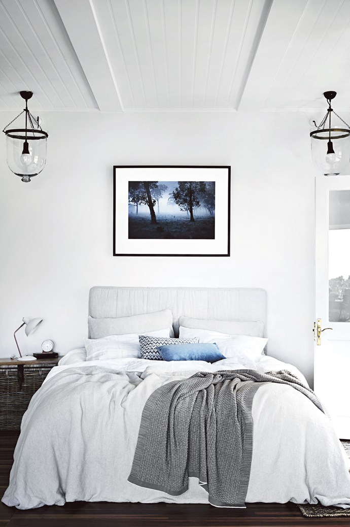 A Mark Lobo 'Ritual' print hangs above the bed, swathed in Abode Living bedlinen and adorned with Linen House cushions. The pendant lights were sourced on  a trip to France. | Photo: Tess Kelly