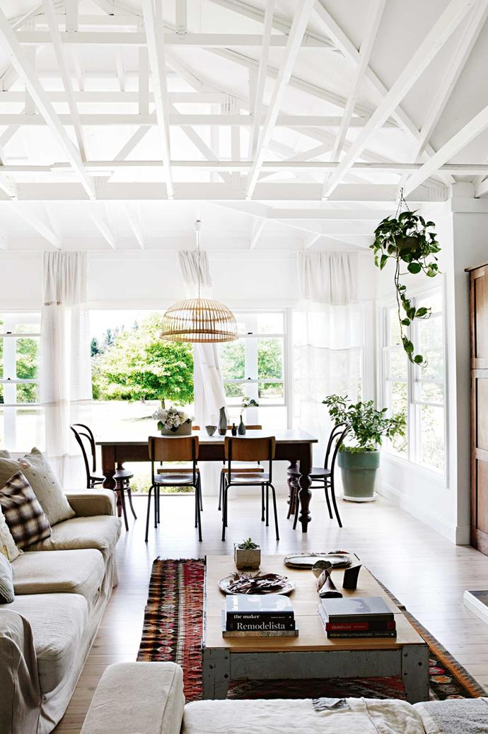 """Comfortable living-room sofas  in neutral tones are stacked with cushions. Alison and Andrew painted their [weatherboard house](https://www.homestolove.com.au/weatherboard-houses-5478