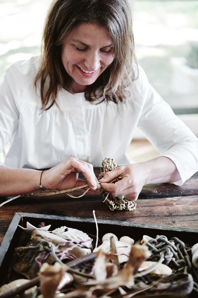 "Kate working with some of her collected pieces, cording natural fibres from a red hot poker plant into a bag.  ""I make really simple things with found objects from around the farm, or the tip,"" says Kate.  