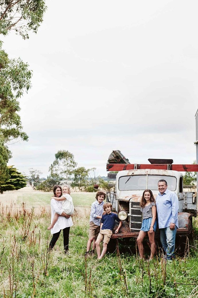 Kate holding Meg, Sid, Gus, Ava and Adrian in front of  the neighbour's vintage truck.