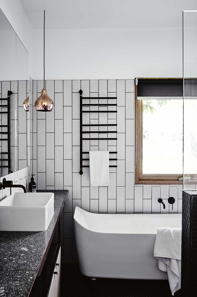 """The bathroom features terrazzo bench tops and subway tiles laid vertically for a modern, yet classic, look. """"We painted the legs of the  bath white,"""" says Penny."""
