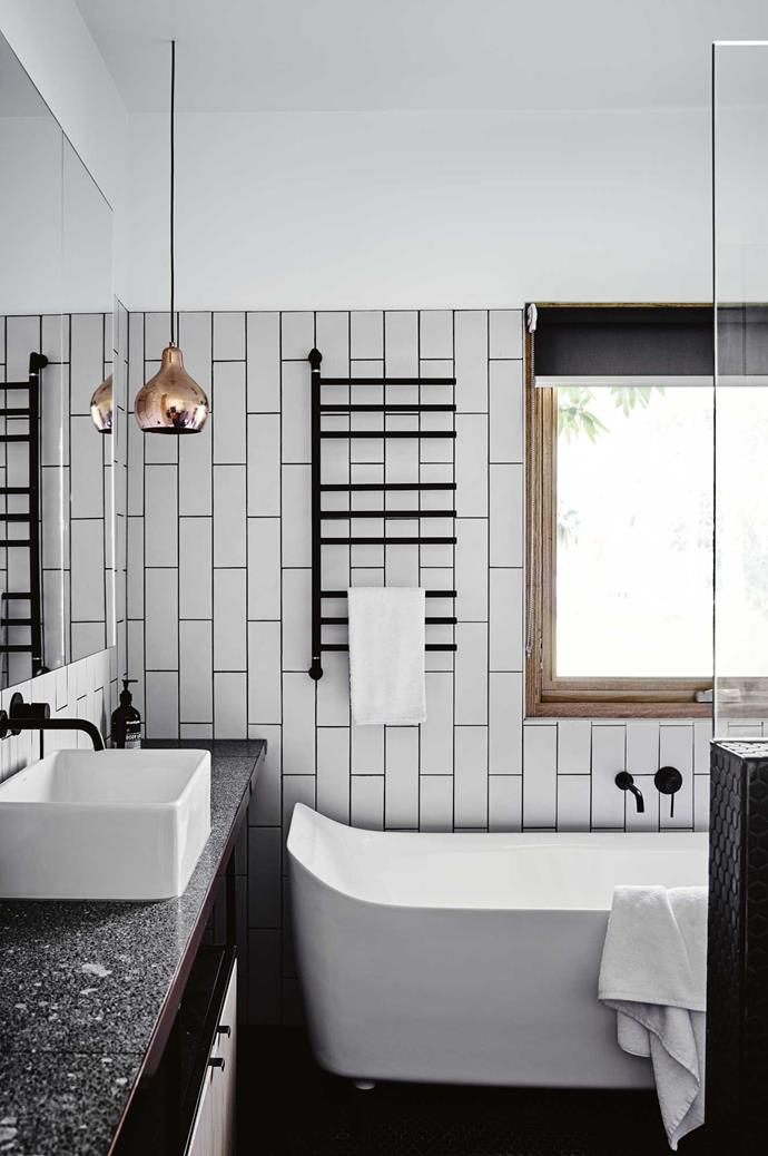 "The bathroom features terrazzo bench tops and subway tiles laid vertically for a modern, yet classic, look. ""We painted the legs of the  bath white,"" says Penny."