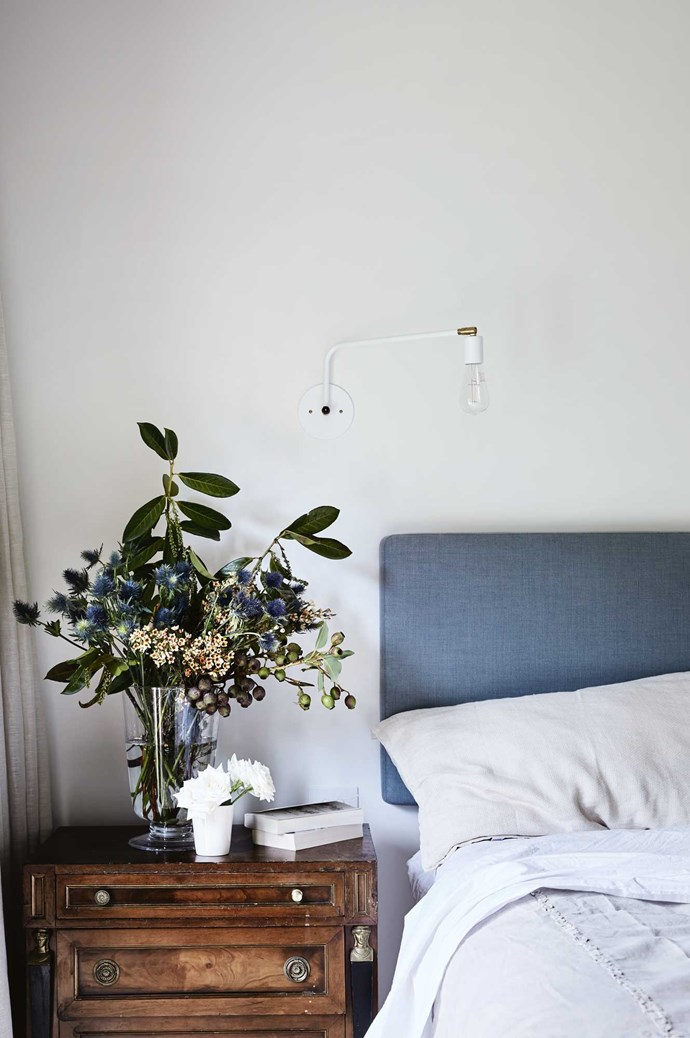 The French linen bedhead in the main bedroom is from Altamira, while the bedside table was a find at Tyabb Packing House. The swivel light above the bed was brought back from the US. | Photo: Sharyn Cairns
