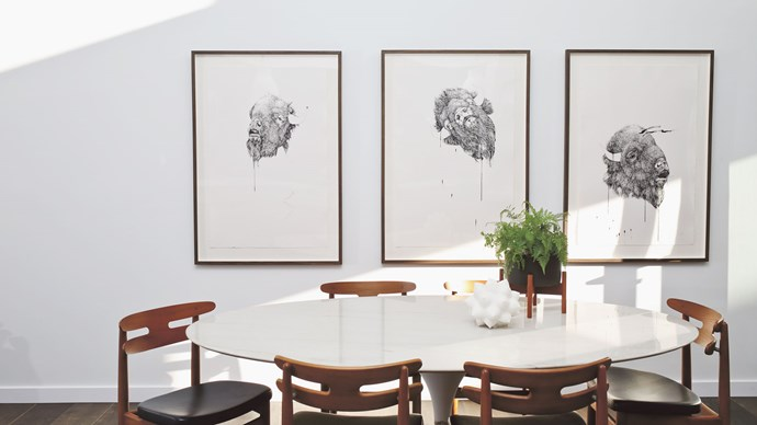 Tip #5: Another way to designate an area is to use the wall space. Here the three pieces of art anchor the dining zone.  An oval or rounded table is a good choice if you like to entertain or often have extra kids joining the family. You can always squeeze a couple of extra chairs around an organic shape. Rounded edges also soften up the space and give a sense of extra room. Where you have a table in a relatively narrow path – in this case leading to the outdoor living space – it's the perfect choice.  | Photo: Anastasia Kariofyllidis