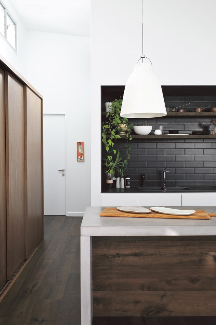 """Tip #6: Going for cabinets with no handles will give you a cleaner, more modern look. The long concrete island bench, including bench seating, was the starting point for Brooke designing the kitchen. """"I knew I wanted to work with Pop Concrete, and we needed a crane to get it in."""" She and Alex love the mix of function and beuaty in this space: """"What I like is the island bench is uninterrupted by a cooktop or a sink – it's one long seamless expanse of benchtop,"""" says Brooke. """"The beauty comes from mixing the beautiful textures and allowing space for purely decorative styling."""" Plus, there's the generous load of built-in storage.  