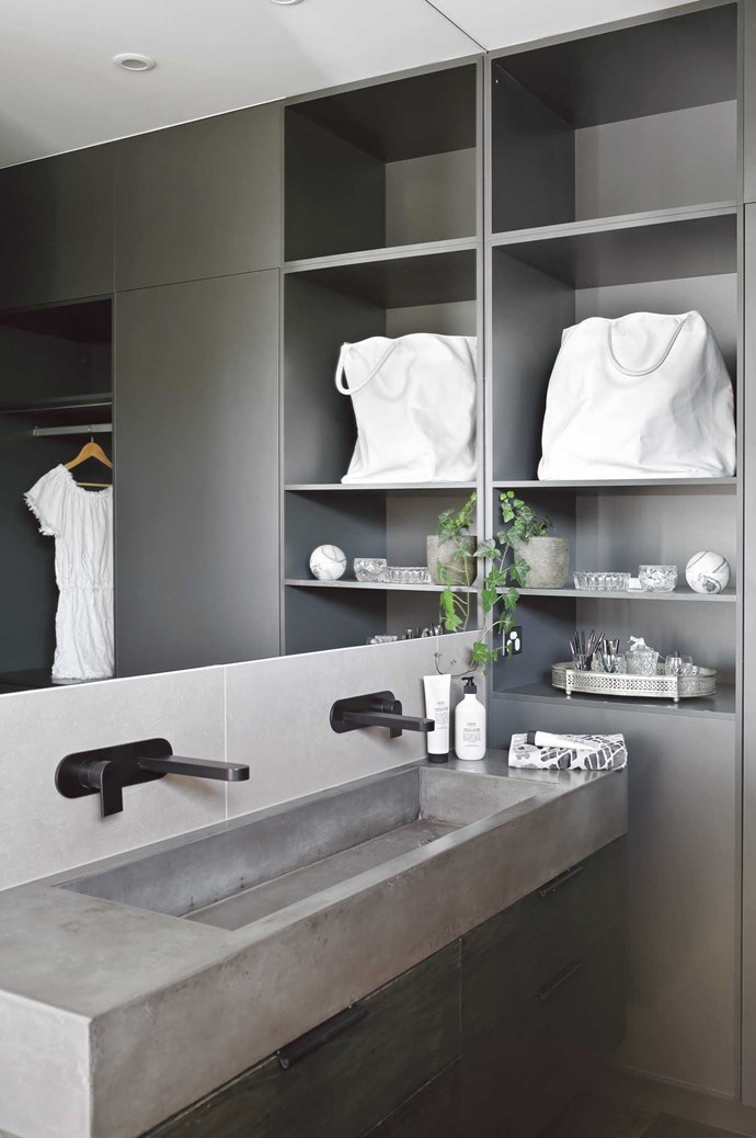 Tip #8: A bigger format frameless mirror will make the space appear larger. The combined sink in the ensuite vanity is a really nice use of a long, thin space and is easy for two people to use at the same time. The bespoke concrete finish really highlights  the black tapware and the open shelving at the end of the basin is practical, which is exactly what you need in a small space.  | Photo: Anastasia Kariofyllidis