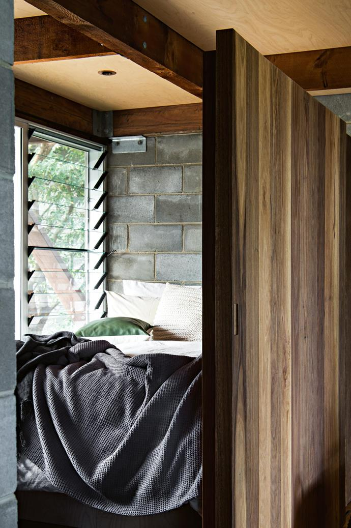 A queen bed, separated from the casual living room by a spotted gum sliding door, features a custom-made bed and the home's original besser blocks as the bedhead.