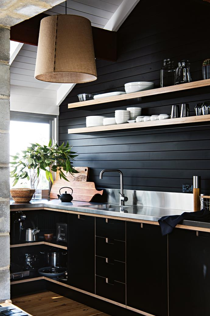 Black plywood cupboards and a stainless steel benchtop give the kitchen a modern feel. The original cypress wood walls were painted with Porter's Paints 'Palm Beach Black' and a custom-made light shade from Paralume was added.