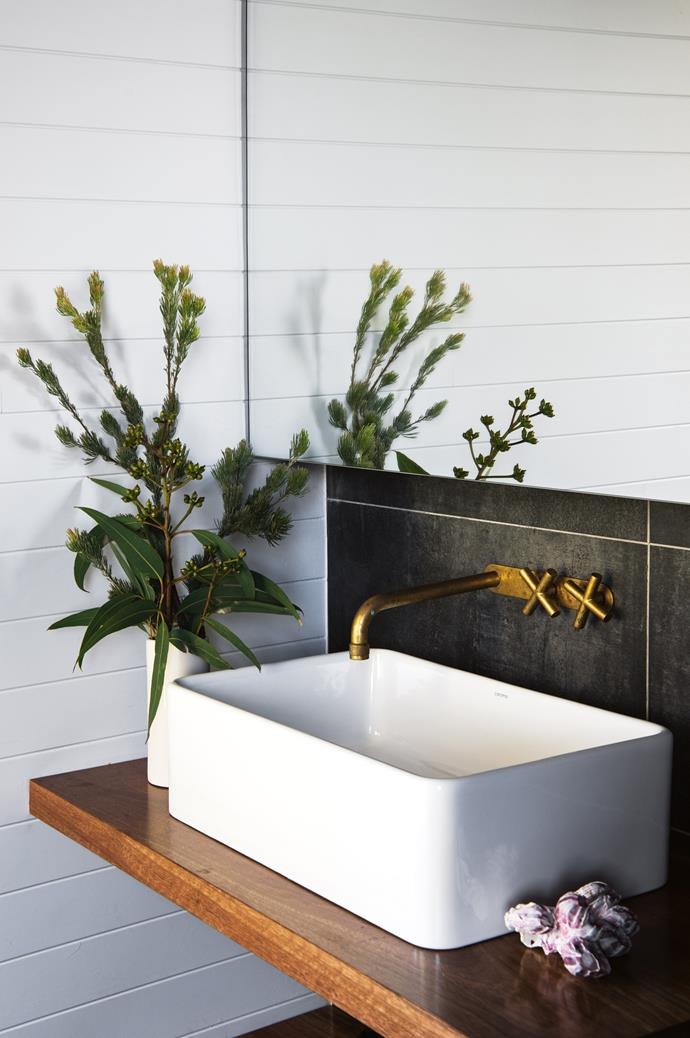 A Brodware tap set with a rumbled brass organic finish hangs over the above-counter basin in the bathroom. The floating counter was custom made in spotted gum.