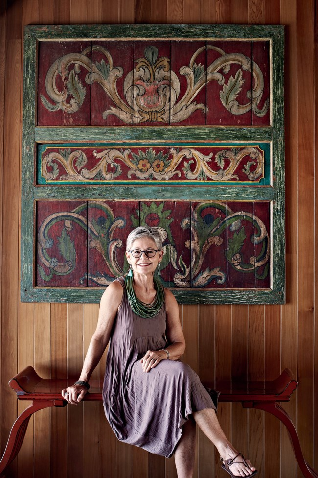 Jo Cockerill sits on a carved Chinese bench before an old Indonesian painted panel. | Photo: Sharyn Cairns