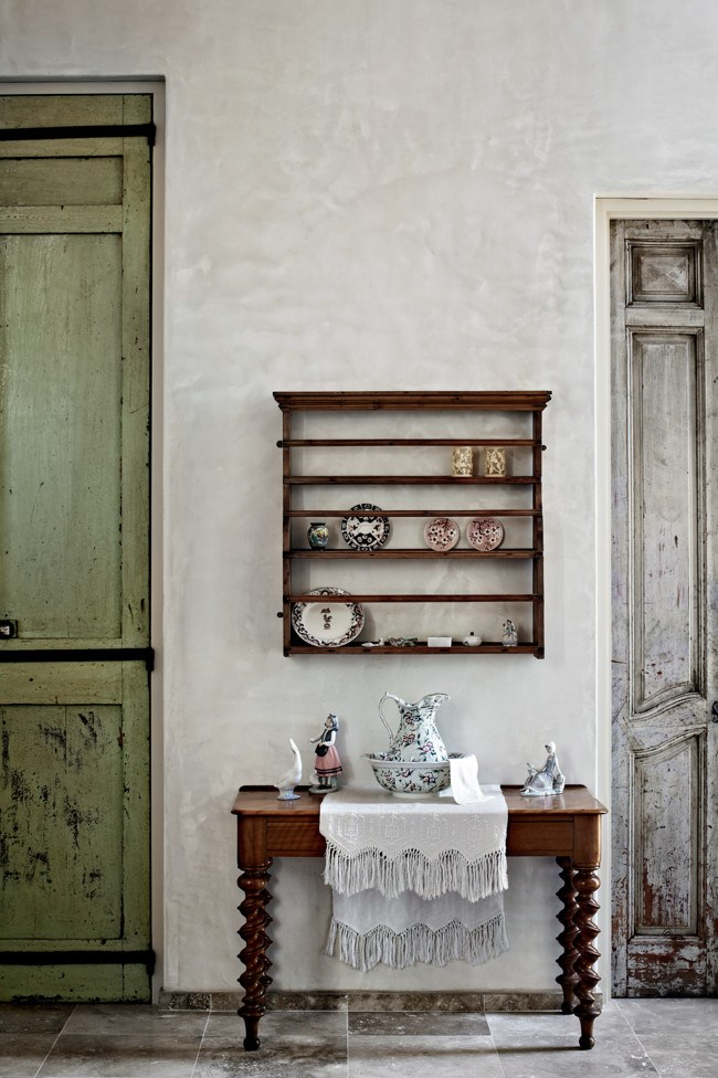 A late 18th-century English walnut desk stands between two old French doors. The shelves hold chinaware inherited from Jo's mother, and the linen was embroidered by her grandmother. | Photo: Sharyn Cairns