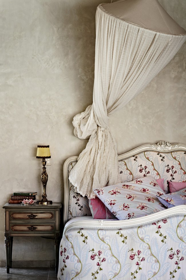 "A French bed, table and lamp in the main bedroom beneath a pretty mosquito net that Jo says ""is far from decorative!"" 