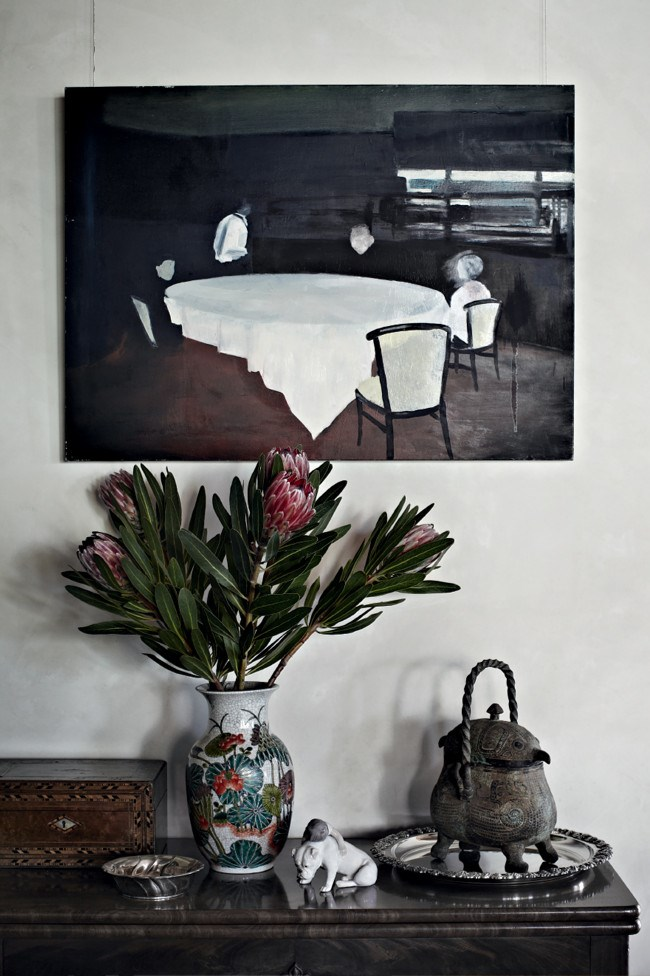 A painting of the Cockerill family at a restaurant by Jo and Ray's son, Leigh, hangs over a Chinese urn for carrying hot coals and a Danish bulldog ceramic. | Photo: Sharyn Cairns
