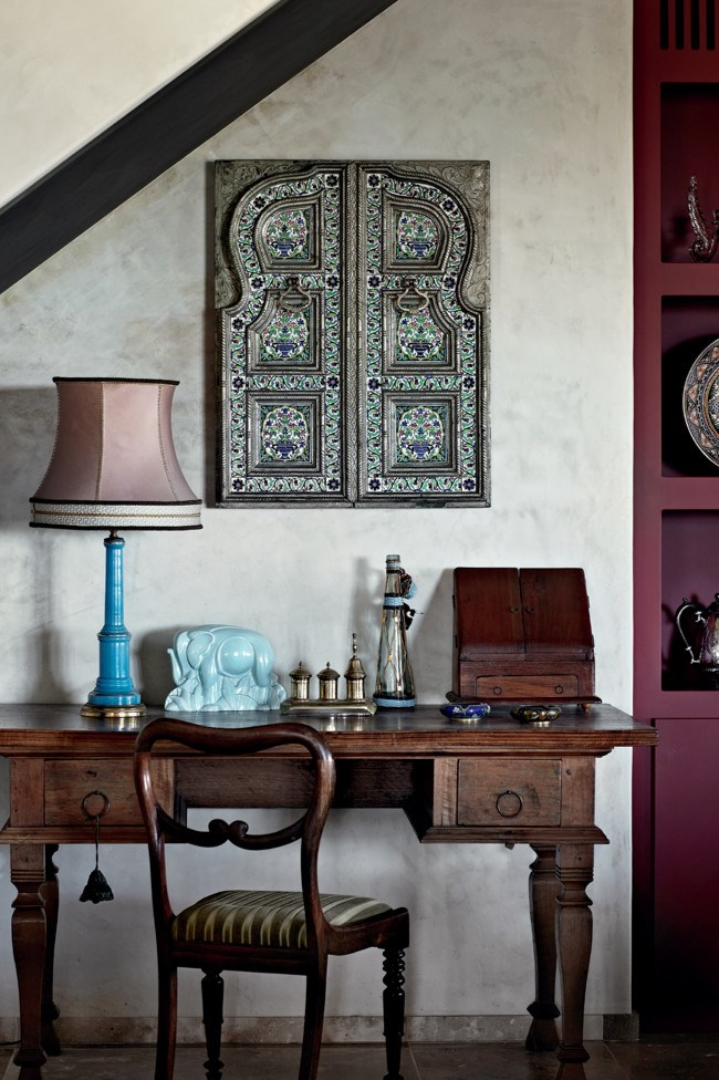 A teak Indonesian desk stands beneath ornate Indian window shutters. | Photo: Sharyn Cairns
