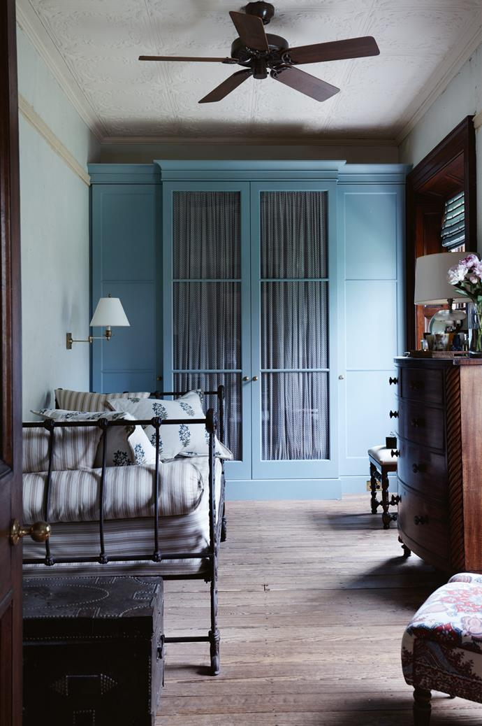 An antique French day bed is the centrepiece in the dressing room, where the wardrobe is painted in Farrow and Ball 'Berrington Blue'.
