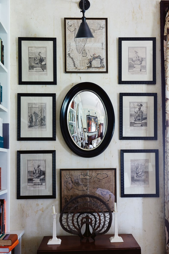 "The library is home to countless [pieces the couple have collected on their travels](https://www.homestolove.com.au/8-interior-trends-from-around-the-globe-6715|target=""_blank"") over the years. Here, arranged around a custom oval convex mirror, are early 17th-century maps of India and The Holy Land, as well as six 17th-century French engravings of maharajas from the Roger Banks-Pye collection. On the table is a wedding headpiece from the Wosera district in Papua New Guinea."