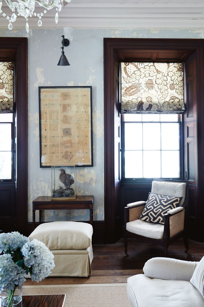 "An artwork by the late Maureen van der Giessen hangs in the library. The [19th-century armchair](https://www.homestolove.com.au/choosing-an-armchair-3851|target=""_blank"") upholstered in blonde horsehair is complemented by a Kuba cloth cushion, made from fabric the couple bought in the Marche aux Puces de Saint-Ouen, France."