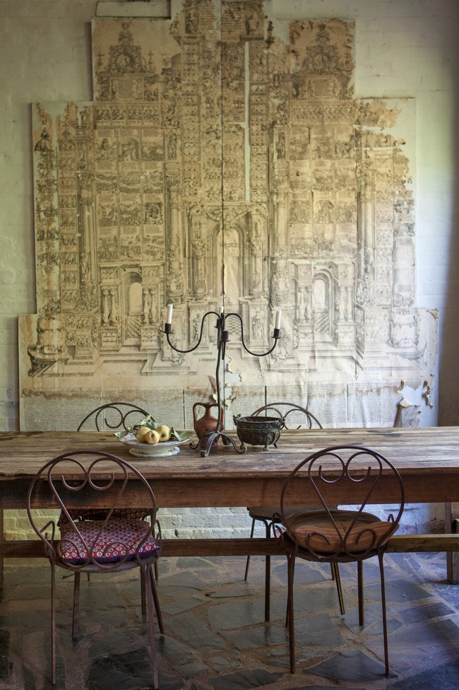 """The unusual artwork came with the house: """"It is paper glued to chipboard and depicts many little scenes within a cathedral-like structure,"""" says Julienne Huntley. On the table stands a candelabra """"found at a garage sale and welded together by a bikie who lived there"""". 