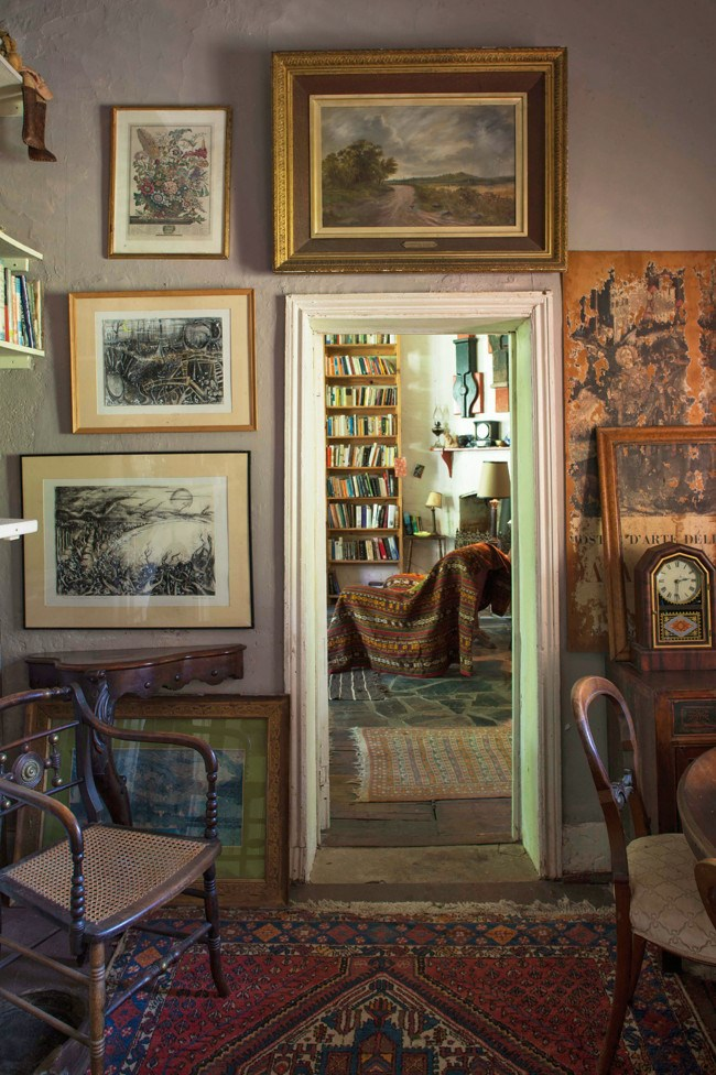 In the 'snuggery', charcoal drawings by Julienne hang beneath a landscape inherited from her grandmother and opposite a cottage clock acquired at auction. | Photo: Simon Griffiths