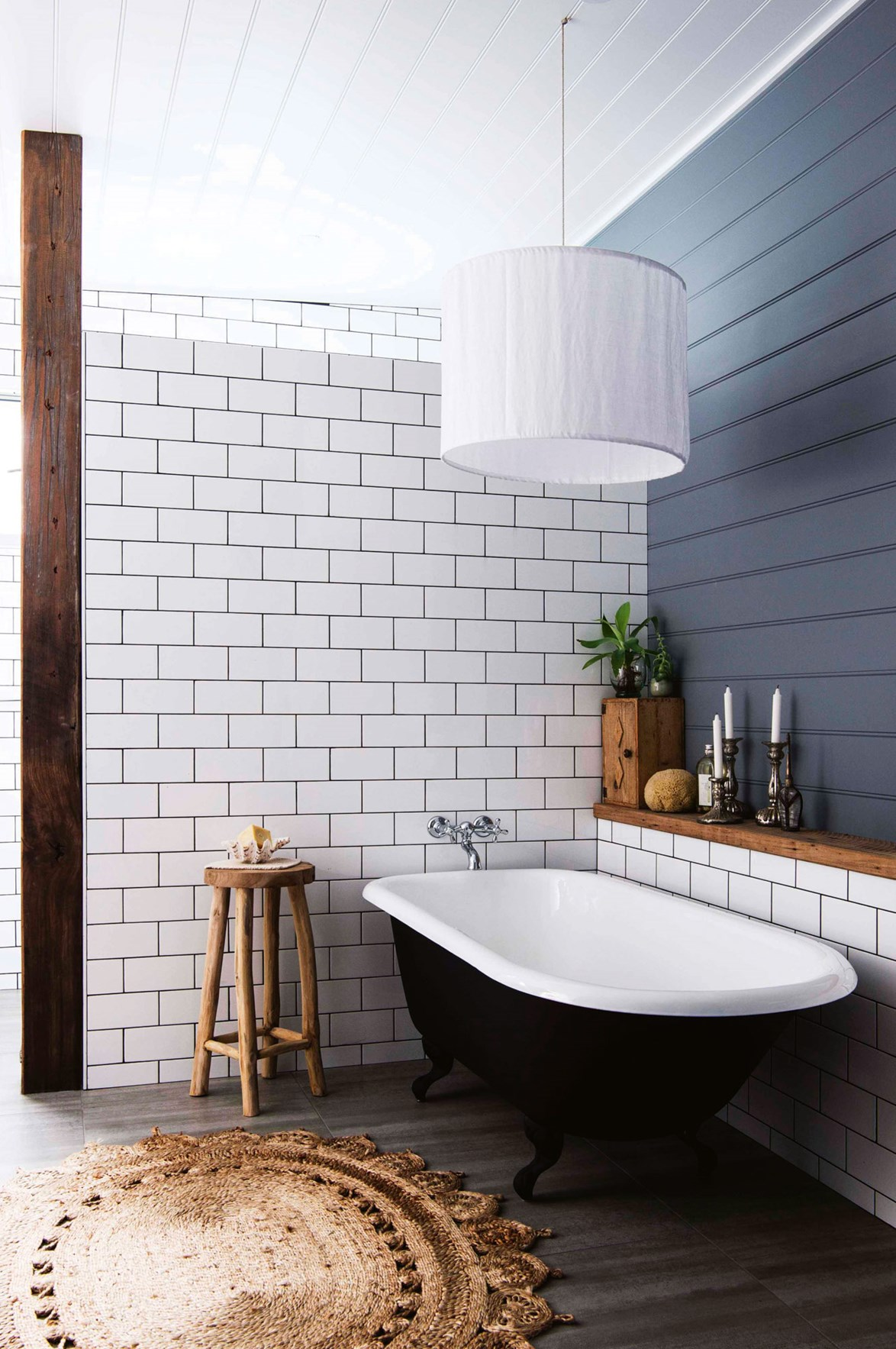 """A freestanding claw-footed tub at a [serene beach house](https://www.homestolove.com.au/serene-nsw-beach-house-filled-with-handmade-furniture-13872 target=""""_blank"""") has been modernised with a lick of black paint, while a handy timber shelf adds texture and functionality to the bathing nook. *Photo: Brigid Arnott / Styling: Vanessa Colyer Tay / Story: Country Style*"""