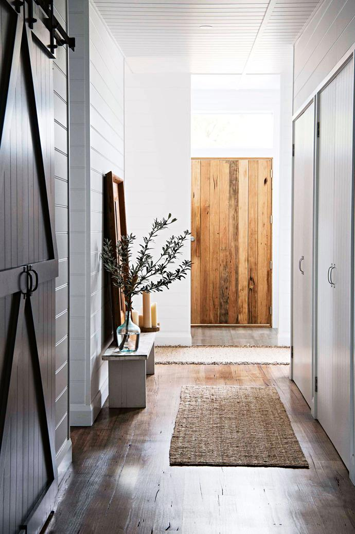 "The heavy timber door opens to a tiled foyer and hallway with hardwood floors. Storage cupboards line one wall, while custom-made [barn doors](https://www.homestolove.com.au/maximise-space-and-style-with-barn-doors-6582|target=""_blank"") lead to the bathroom on the other."