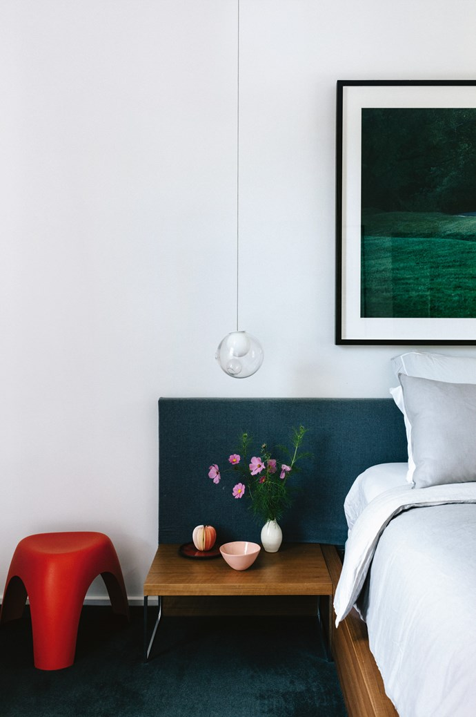 Jacqui Henshaw's photograph of the Coliban River hangs in the main bedroom. An original apple from Japan and [Mud Australia](https://mudaustralia.com/) bowl decorate the side table with a pendant light from [Hub](http://www.hubfurniture.com.au/) hovering above. | Photo: Marnie Hawson