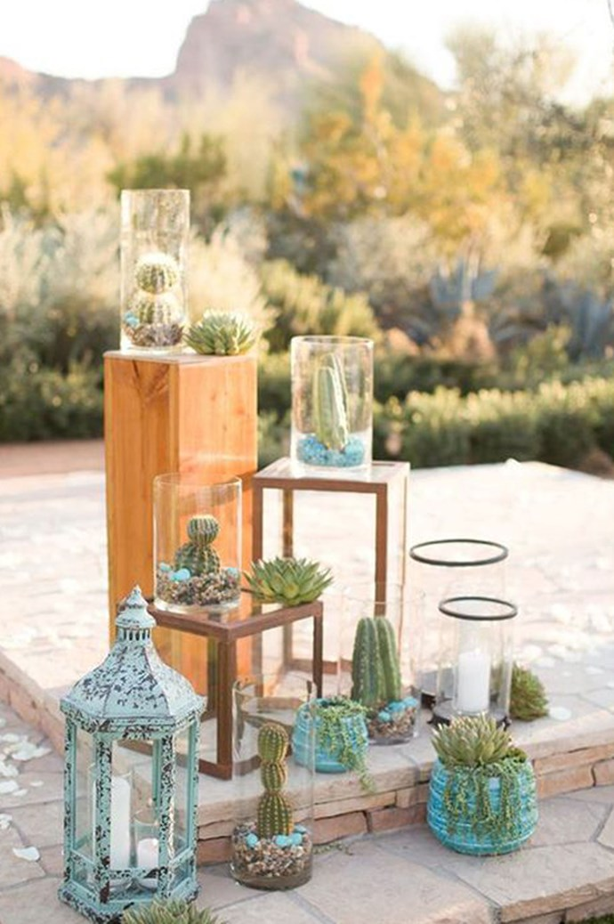Don't limit cacti to the table – they make an equally striking display when grouped together in glass vases alongside candles and lanterns. Image via [Happy Wedd](http://happywedd.com/)