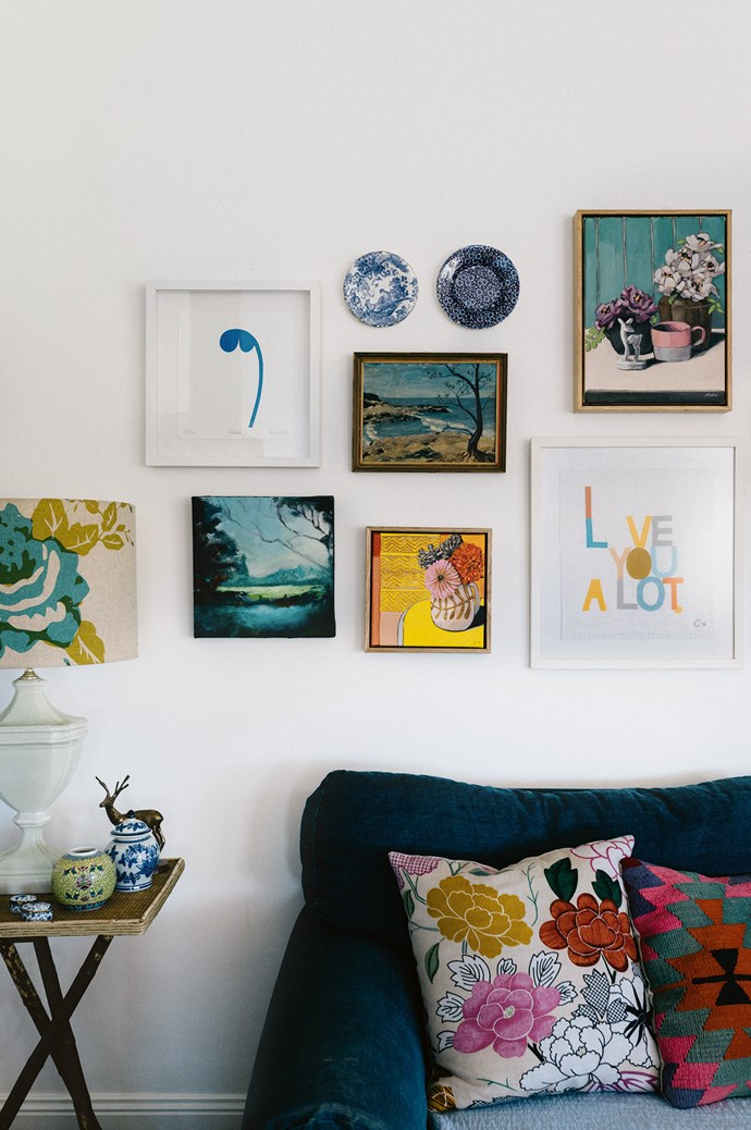 The gallery wall in the living area features work by artists Rachel Castle, Sam Michelle and Ali Wood. It has morphed over the past year in a mixture of landscapes and still life paintings.  | Photo: Marnie Hawson