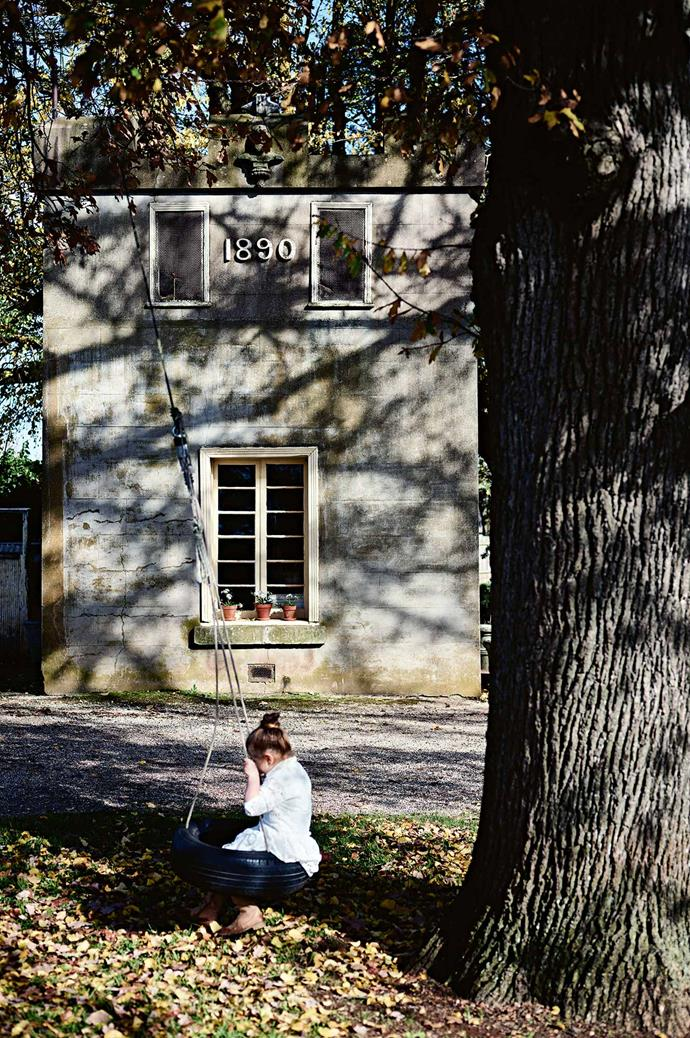 Isobel swings on the oak tree in the driveway, against the facade of the 1890s cool room.