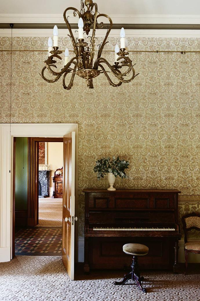 The drawing room in the home's front wing, with its original wallpaper and drapes, set the palette for the rest of the renovations. Jane and Geordie tracked down authentic light fittings like this chandelier from antique specialists. The piano belonged to Jane's mother.